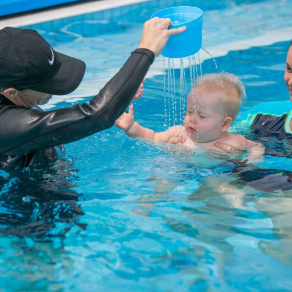 Instructor pouring water over babys head