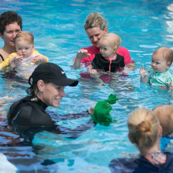 Blue water babies group lesson with swimming instructor