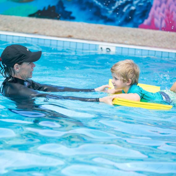 Swimming insructor and child on floatation device