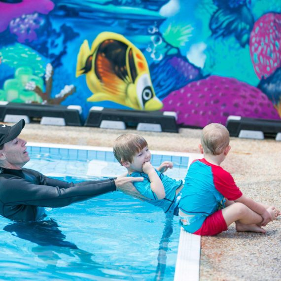 Instructor catching child as he lay back into the pool