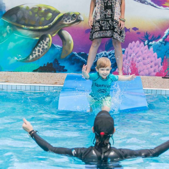 Child jumping into the pool with instructor