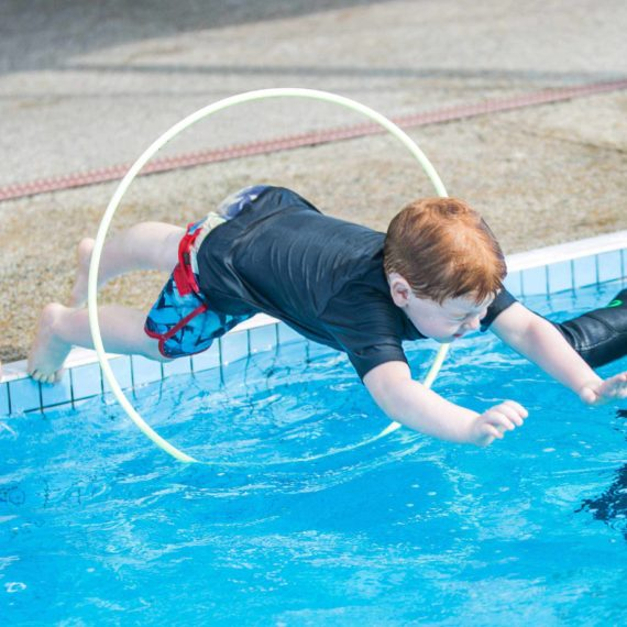 Child jumping into pool through a hoop