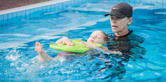 Gina teaching a child swimming techniques