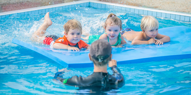 Children on floatation device learning to swim