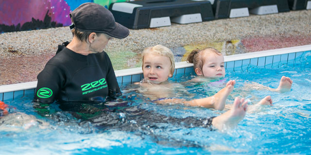 Children listening to Ginas instruction in the pool